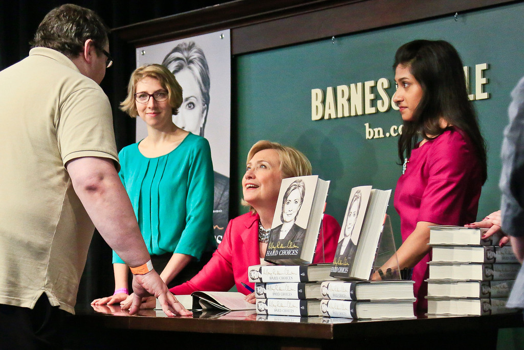 """. Sean Brennan, far left, chats with HiIlary Rodham Clinton, center, before receiving a signed copy of her new book \""""Hard Choices,\"""" on Tuesday June 10, 2014, at Barnes and Noble bookstore in New York.  Brennan, 41 from Queens, N.Y., was first in line to meet Clinton, spending the night after arriving 2:30 p.m. yesterday.  \""""I like Hillary Clinton,\"""" said Brennan.  \""""There aren\'t many people worth coming out for twenty four hours before hand to see, but she is one of them.\""""  (AP Photo/Bebeto Matthews)"""