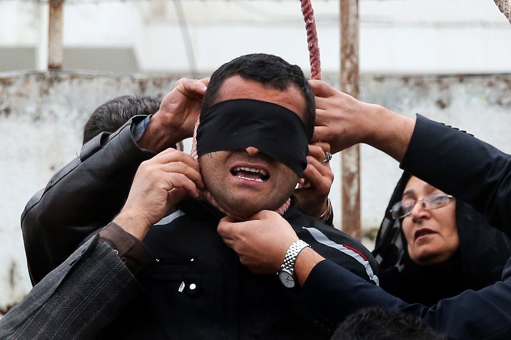 . The mother (R) of Abdolah Hosseinzadeh, who was murdered in 2007, removes the noose with the help of her husband from around the neck of Balal, who killed her son, during the execution ceremony in the northern city of Nowshahr on April 15, 2014, sparing the life of her son\'s convicted murderer. The dramatic events followed a rare public campaign to save the life of Balal, who at 19 killed another young man, Abdollah Hosseinzadeh, in a street fight with a knife back in 2007. AFP PHOTO/ARASH KHAMOOSHI/AFP/Getty Images