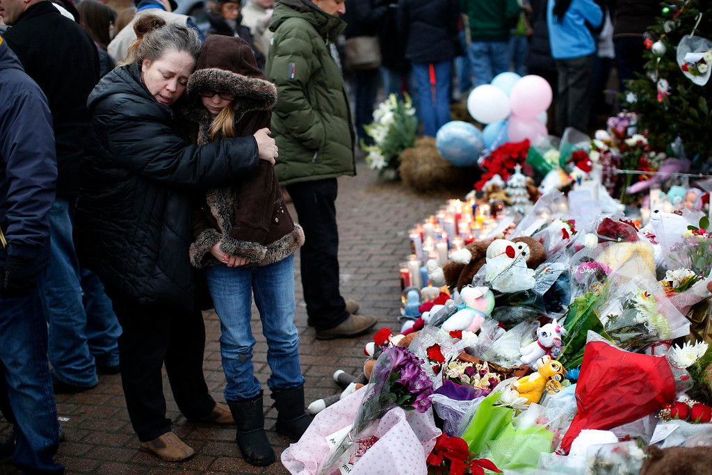 . A mother embraces her daughter as they stand at a makeshift memorial near Sandy Hook Elementary School for the victims of a school shooting in Newtown, Connecticut December 16, 2012. Twelve girls, eight boys and six adult women were killed in the shooting on Friday at the Sandy Hook Elementary School in Newtown.  REUTERS/Mike Segar