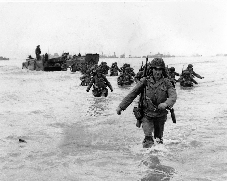 . U.S. infantrymen wade through the surf as they land at Normandy in the days following the Allies\' June 1944, D-Day invasion of occupied France. An allied ship loaded with supplies and reinforcements waits on the horizon.  (AP Photo/Bert Brandt)