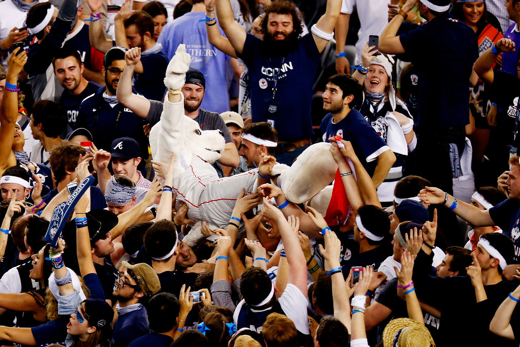 . ARLINGTON, TX - APRIL 07: Connecticut Huskies fans celebrate with the mascot on the court after defeating the Kentucky Wildcats 60-54 in the NCAA Men\'s Final Four Championship at AT&T Stadium on April 7, 2014 in Arlington, Texas.  (Photo by Tom Pennington/Getty Images)