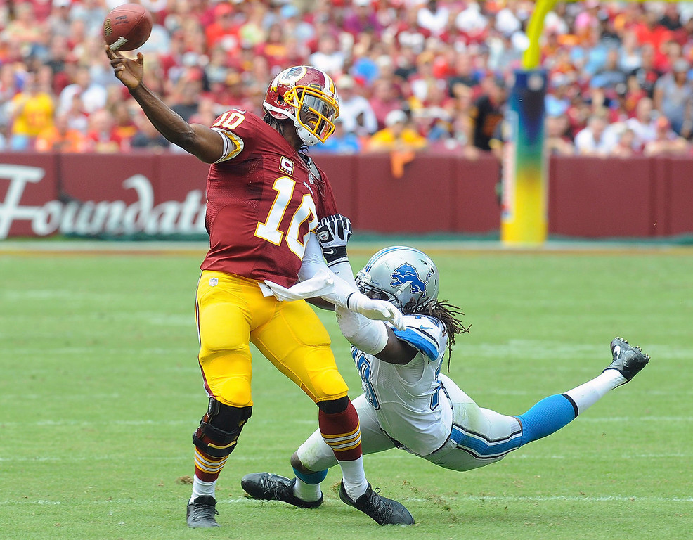 . Washington Redskins quarterback Robert Griffin III is pulled to the turf by Detroit Lions defensive end Willie Young during the first half of a NFL football game in Landover, Md., Sunday, Sept. 22, 2013. (AP Photo/Richard Lipski)