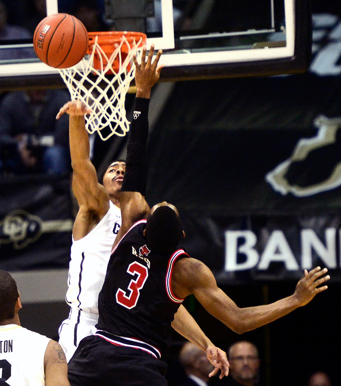 . University of Colorado\'s  Spencer Dinwiddie (25) blocks a shot against Arkansas State\'s Brandon Reed (3)during their game at the Coors Events Center on the CU Boulder Campus in Boulder, Colorado on November 18, 2013.  Photo by Paul Aiken / The Boulder Daily Camera.