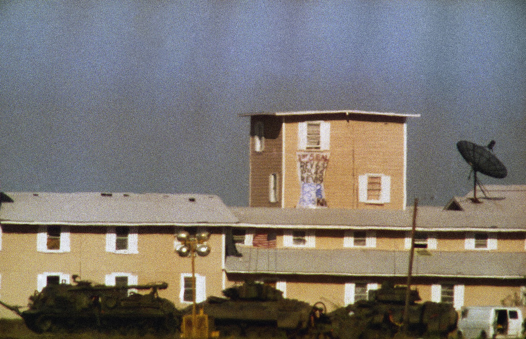 ". Two unidentified men appear between Bradley armored vehicles in front of the Branch Davidian compound near Waco, Texas on Saturday, April 11, 1993. Federal authorities erected barbed wire around the compound to prevent cult members from escaping. The banner hanging from the compound window reads: ""1st Seal, Rev 6:12, PS 45, Rev 19, PS 2, PS 18, PS 35, KJV,\"" which refers to several verses from Psalms and revelation in the Bible. KJV refers to the King James version of the Bible. Authorities refused to comment on significance of the banner. (AP Photo/Rick Bowmer)"
