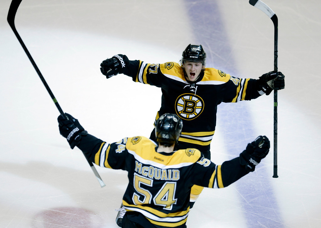 . Boston Bruins defenseman Adam McQuaid (54) celebrates his goal against the Pittsburgh Penguins with defenseman Torey Krug, rear, during the third period of Game 4 in the Eastern Conference finals of the NHL hockey Stanley Cup playoffs, in Boston on Friday, June 7, 2013. (AP Photo/Charles Krupa)