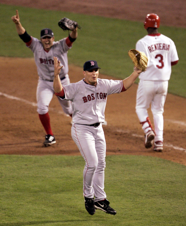 . Boston Red Sox pitcher Keith Foulke, center, and first baseman Doug Mientkiewicz, left, celebrate after St. Louis Cardinals\' Edgar Renteria (3) grounded out to end the ninth inning and give Boston a 3-0 win and a sweep of the World Series, Wednesday Oct. 27, 2004, in St. Louis. (AP Photo/Mark Humphrey)