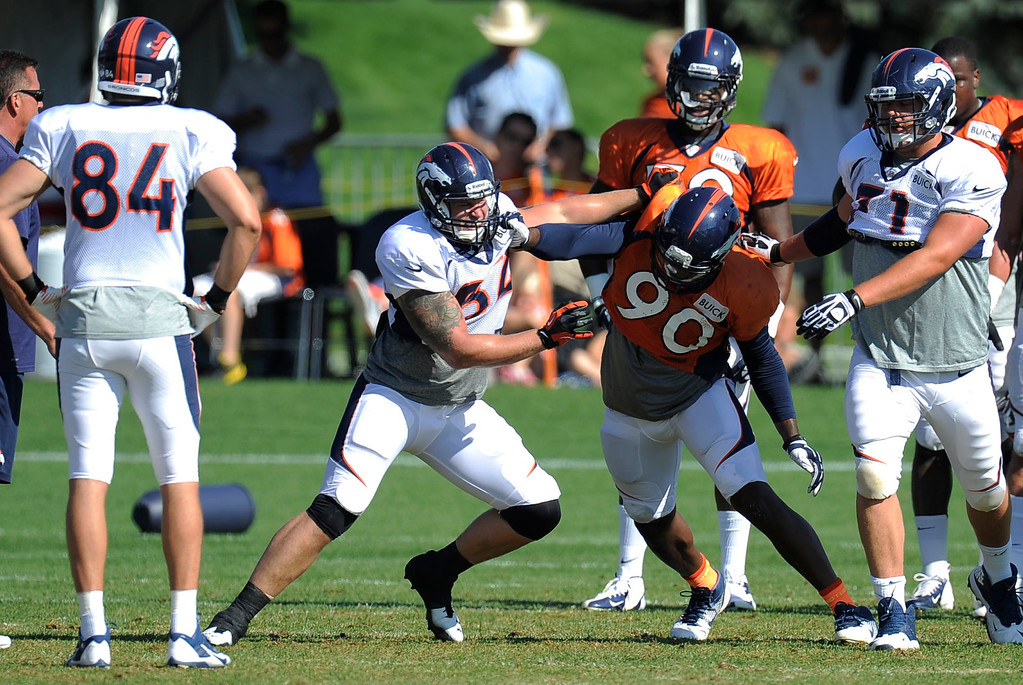 . Denver Broncos TE Jake O\'Connell (82) blocks Shaun Phillips (90) during training camp August 13, 2013 at Dove Valley. (Photo By John Leyba/The Denver Post)