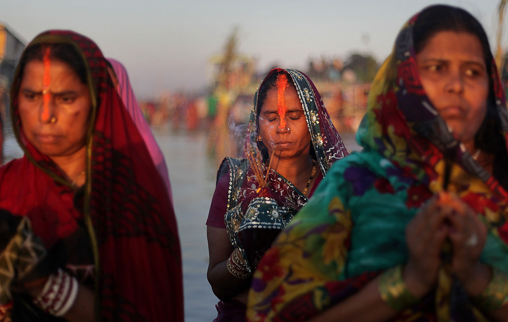 . Hindu devotees perform rituals to the setting sun in the River Brahmaputra during Chhath Puja festival in Gauhati, India, Friday, Nov. 8, 2013.  (AP Photo/Anupam Nath)