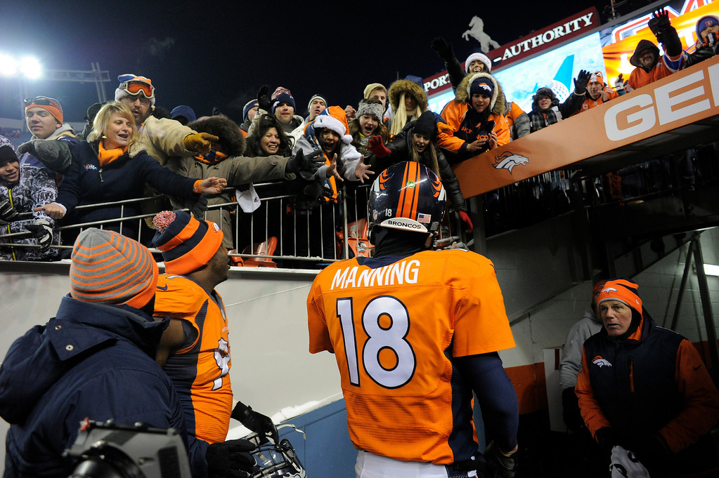 . DENVER, CO - DECEMBER 08: Denver Broncos quarterback Peyton Manning (18) throws his gloves to the fans as he heads for the locker room. The Denver Broncos take on the Tennessee Titans at Sports Authority Field at Mile High in Denver on December 8, 2013. (Photo by John Leyba/The Denver Post)