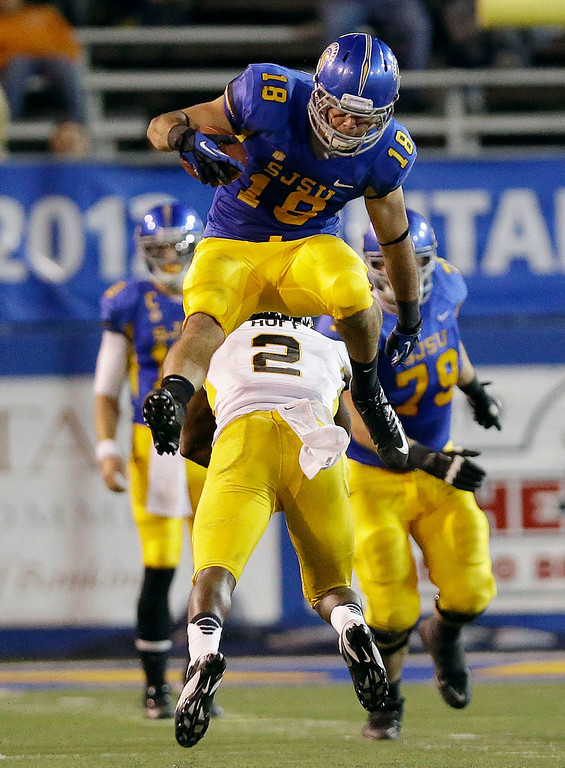 . San Jose State tight end Billy Freeman, top, leaps over Wyoming safety Marqueston Huff (2) during the second half of an NCAA college football game on Saturday, Oct. 26, 2013, in San Jose, Calif. San Jose State won 51-44. (AP Photo/Marcio Jose Sanchez)