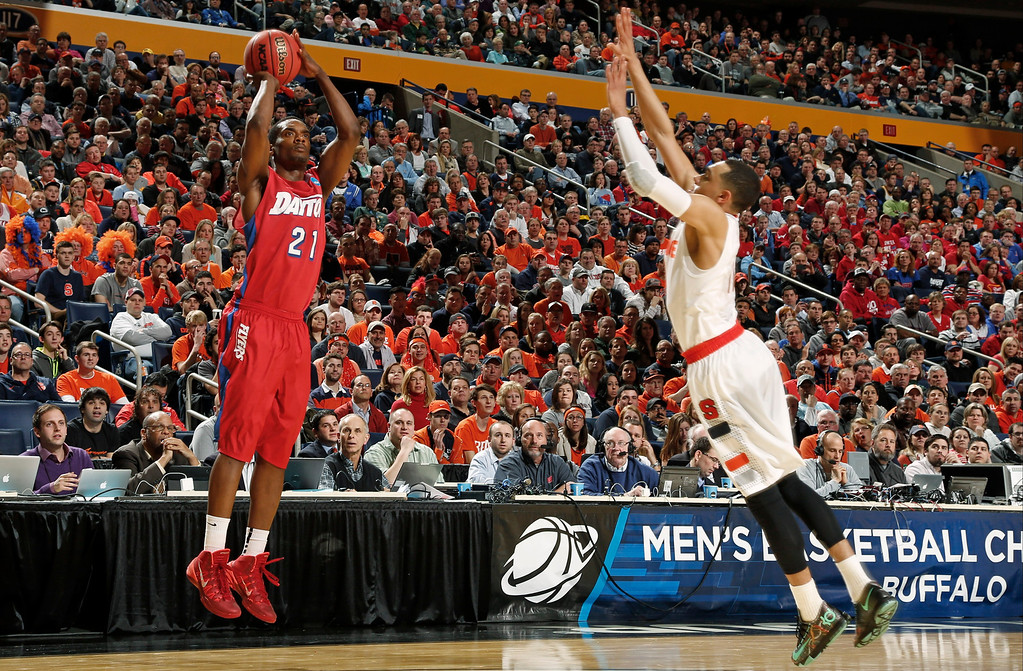. Dayton\'s Dyshawn Pierre (21) shoots over Syracuse\'s Tyler Ennis (11) during the first half of a third-round game in the NCAA men\'s college basketball tournament in Buffalo, N.Y., Saturday, March 22, 2014. (AP Photo/Bill Wippert)