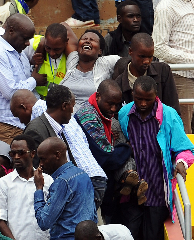 . Men help carry a crying woman at the Amahoro stadium in Kigali on April 7,2014, during a ceremony marking the 20th anniversary of Rwanda\'s genocide.  AFP PHOTO / SIMON  MAINA/AFP/Getty Images