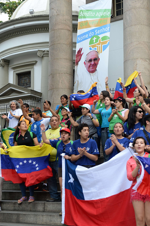 . Faithfuls with flags of Chile (front R) and Venezuela wait for Pope Francis to pass in an open-top jeep after his arrival in Rio de Janeiro on July 22, 2013.  AFP PHOTO / TASSO  MARCELO/AFP/Getty Images