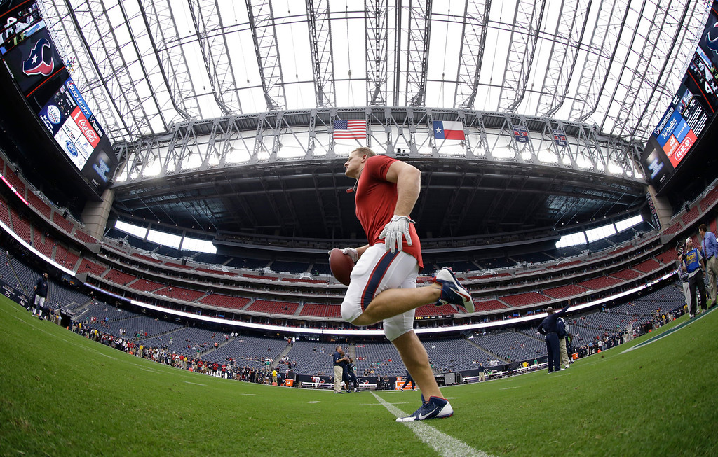 . In this photo taken with a fisheye lens, Houston Texans\' J.J. Watt warms us before an NFL football game against the Seattle Seahawks, Sunday, Sept. 29, 2013, in Houston. (AP Photo/David J. Phillip)