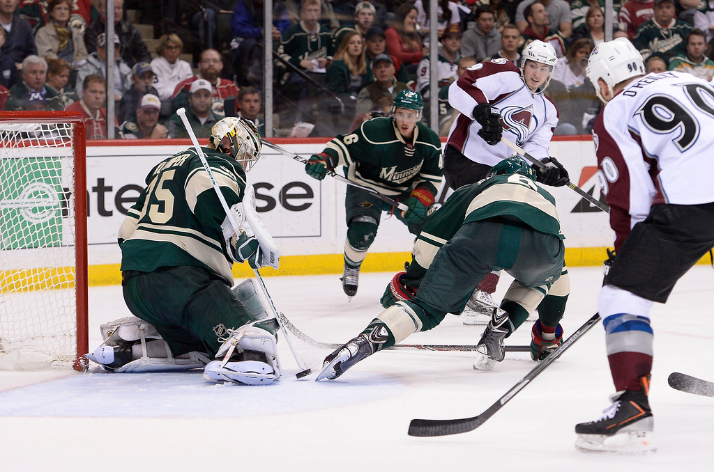 . Colorado Avalanche center Matt Duchene (9) centers the puck as it goes between the skate of Minnesota Wild goalie Darcy Kuemper (35) and Colorado Avalanche defenseman Erik Johnson (6) during the second period April 28, 2014 in Game 6 of the Stanley Cup Playoffs at Xcel Energy Center.  (Photo by John Leyba/The Denver Post)