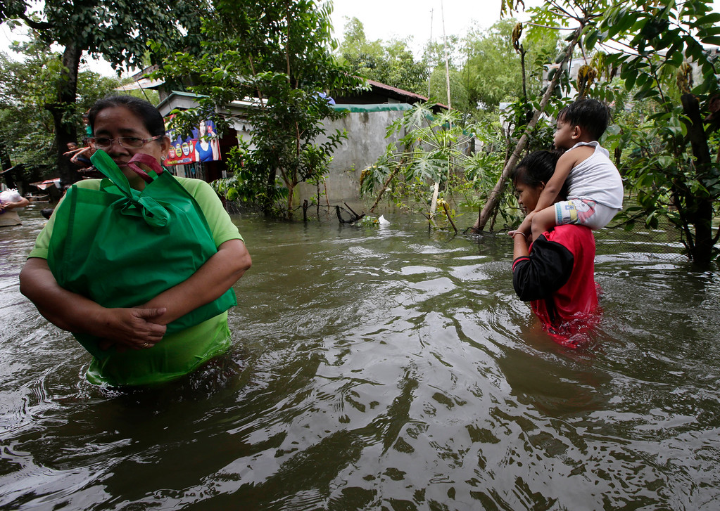 . A resident, left, wades through floodwaters after receiving relief goods from a non-government organization as another resident piggybacks a child to spend the night at an evacuation center at Calumpit township, Bulacan province, north of Manila, Philippines Thursday Aug.22, 2013. Torrential rains brought the Philippine capital to a standstill last Monday, submerging areas in waist-deep floodwaters and making streets impassable to vehicles, while thousands of people in northern regions fled to emergency shelters. Officials reported more than a million people were affected by the flooding in at least five provinces aside from the Philippine capital. (AP Photo/Bullit Marquez)