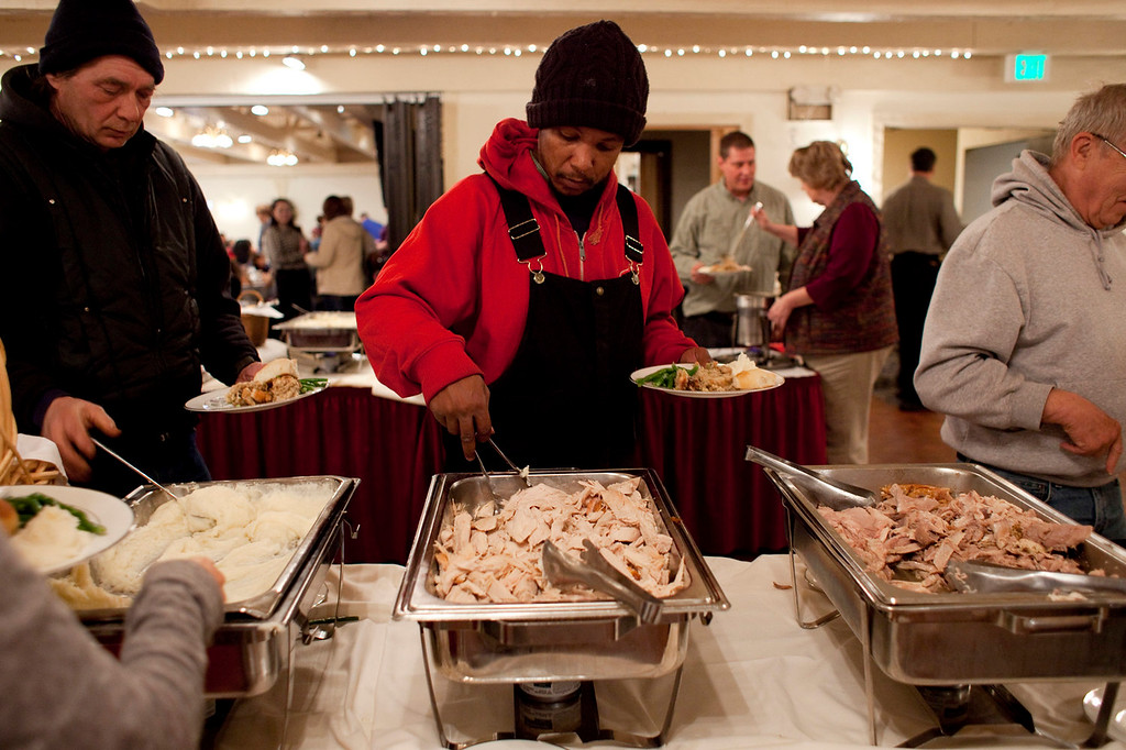. Marcus Moore of Cassopolis, Mich., fills loads up his plate with turkey at the Matterhorn Restaurant in Elkhart, Ind. on Thursday, Nov. 28, 2013. The restaurant, along with Salvation Army, served food from 11 a.m. to 2 p.m., and with hundreds attending, it was the largest meal in Elkhart for the day. Moore moved to Elkhart just over four months ago. (AP Photo/The Truth, Jon Garcia)