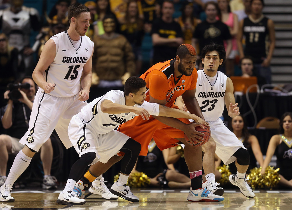 . LAS VEGAS, NV - MARCH 13:  Joe Burton #11 of the Oregon State Beavers is defended by Shane Harris-Tunks #15, Askia Booker #0 and Sabatino Chen #23 of the Colorado Buffaloes in the first half during the first round of the Pac 12 Tournament at the MGM Grand Garden Arena on March 13, 2013 in Las Vegas, Nevada.  (Photo by Jeff Gross/Getty Images)