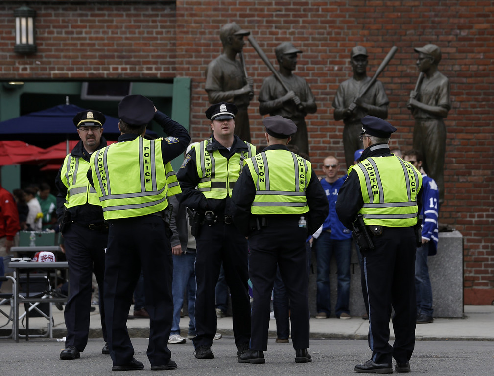 . Police officers stand near statues of fromer Boston Red Sox greats, from left, Ted Williams, Bobby Doerr, Johnny Pesky and Dom DiMaggio during a baseball game between the Kansas City Royals and the Boston Red Sox, the first game held in the city following the Boston Marathon explosions, Saturday, April 20, 2013, in Boston.  Police captured Dzhokhar Tsarnaev, 19, the surviving Boston Marathon bombing suspect, late Friday, after a wild car chase and gun battle earlier in the day left his older brother dead.  (AP Photo/Julio Cortez)