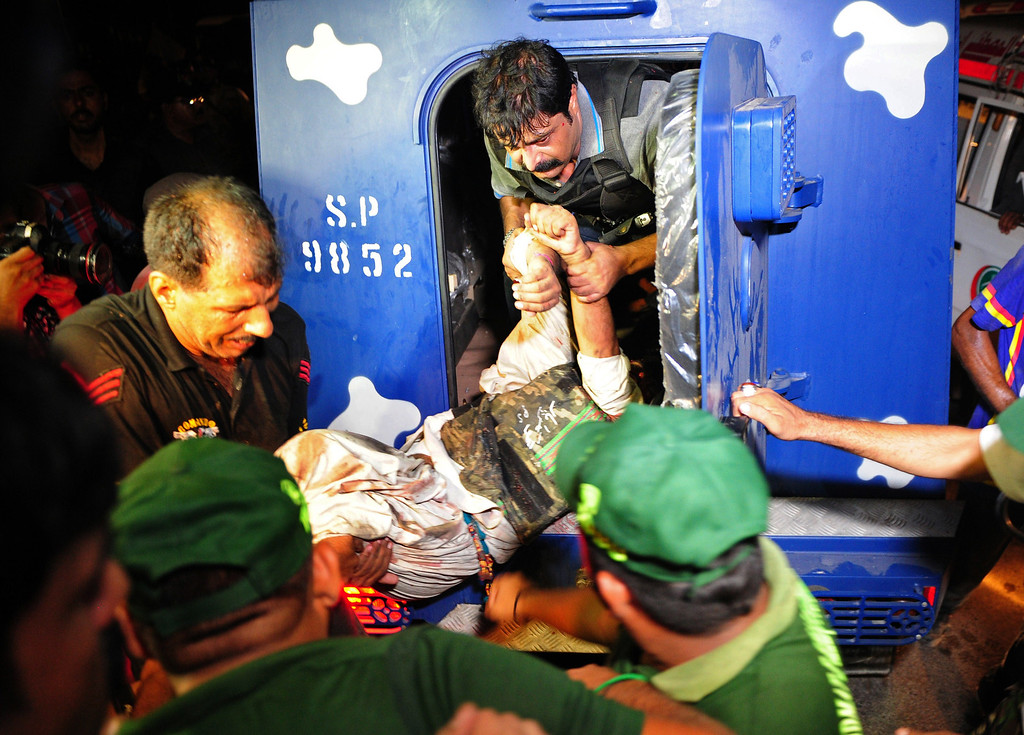 . Pakistani policemen move a wounded colleague outside the Karachi airport terminal following an assault by militants in Karachi late on June 8, 2014.  AFP PHOTO/Asif  HASSAN/AFP/Getty Images