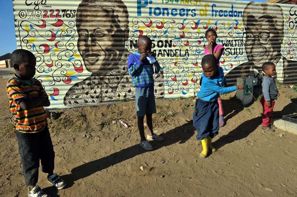 . Children play in front of a mural showing former South African president Nelson Mandela on June 26, 2013  in Soweto, as the former president spends his 19th day in  the Mediclinic heart hospital in Pretoria. Emotional crowds gathered outside the hospital where Nelson Mandela lay in critical condition Wednesday, as relatives and clan elders made preparations for the revered former South African leader\'s final journey.  Singing supporters amassed outside the Pretoria hospital where the 94-year-old anti-apartheid hero was fighting for his life. ALEXANDER JOE/AFP/Getty Images