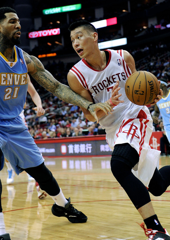 . Houston Rockets\' Jeremy Lin, right, drives the ball past Denver Nuggets\' Wilson Chandler (21) in the second half of an NBA basketball game Wednesday, Jan. 23, 2013, in Houston. Denver won 105-95. (AP Photo/Pat Sullivan)