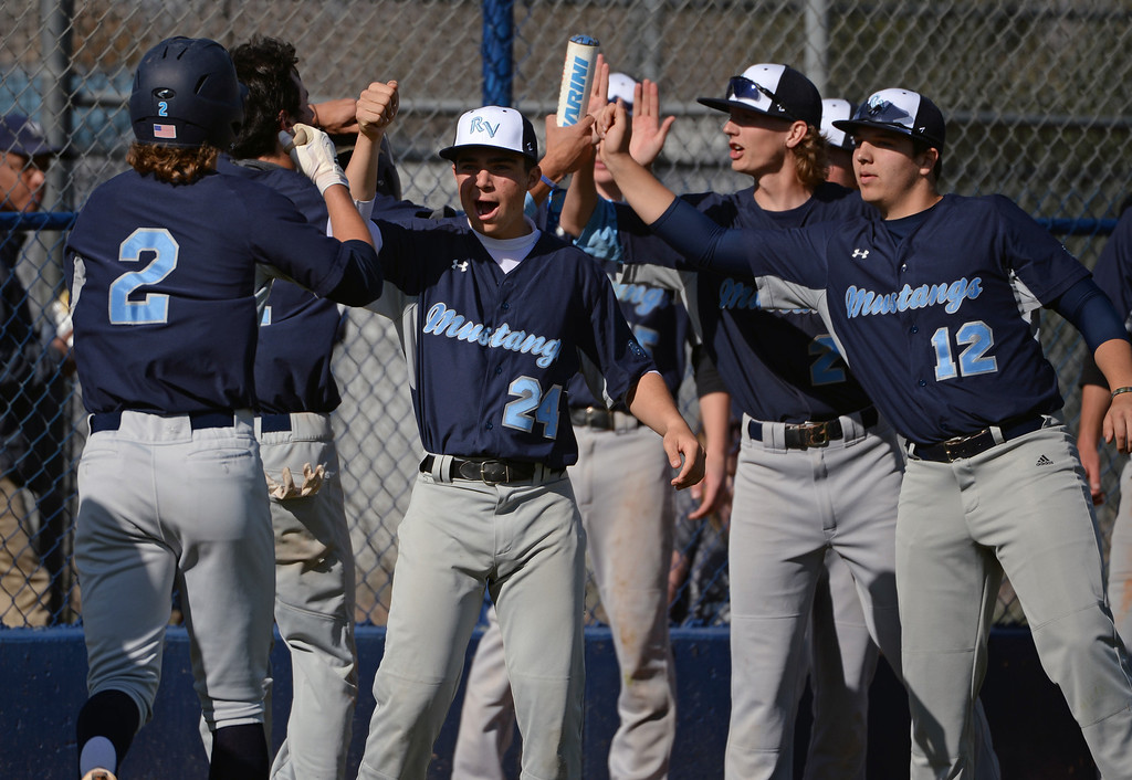 . LITTLETON, CO - APRIL 16,  2014: Ralston Valley Mustangs\' teammates  high five center fielder Jacob Gallegos after he stole home in the top of the second inning in their game against the Columbine Rebels  at Columbine High School in Littleton, Co on April 17, 2014. Columbine pitcher Blake Weiman had a great game and was taken out in the fifth inning when the Rebels were up 8 to 1 over the Mustangs. (Photo By Helen H. Richardson/ The Denver Post)