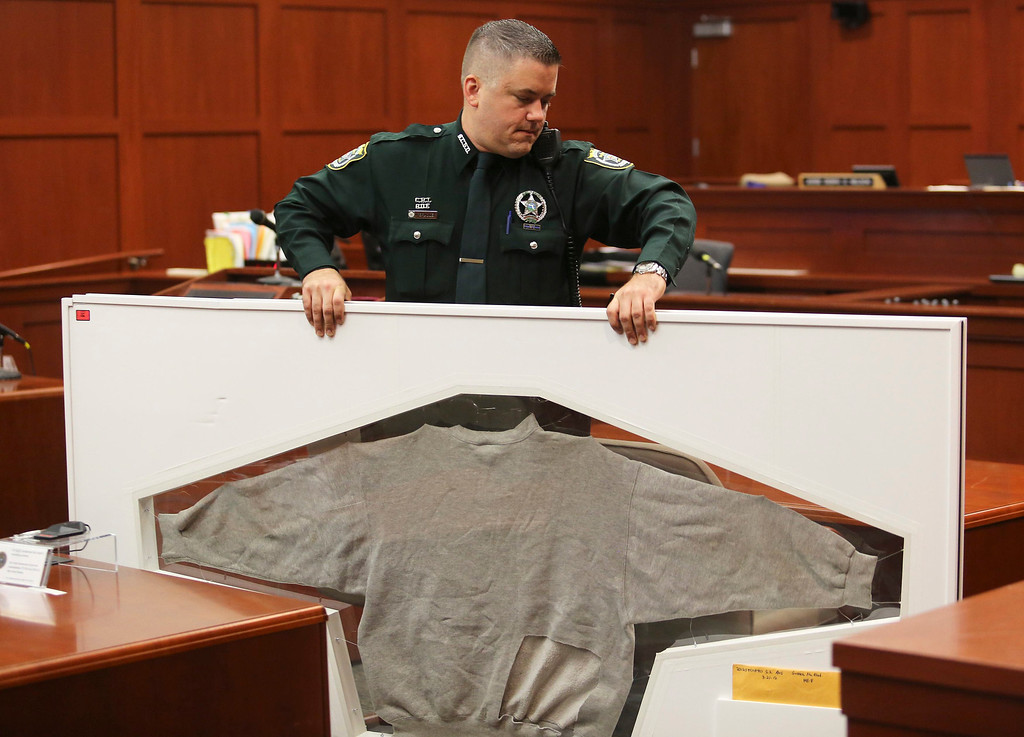 . A Seminole County Sheriff\'s deputy carries Trayvon Martin\'s shirt as trial evidence is moved out of the courtroom in Sanford, Florida July 13, 2013 during the trial of George Zimmerman in the shooting death of Trayvon Martin.  Zimmerman has been charged with second-degree murder for the 2012 shooting death of Trayvon Martin.  REUTERS/Joe Burbank/Pool