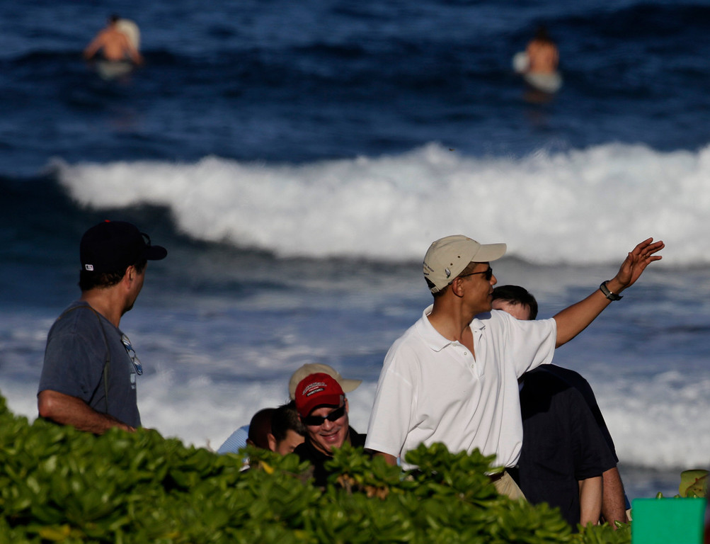 . President Barack Obama, right, waves on Pyramid Rock beach on Marine Corps Base Hawaii in Kaneohe Bay, Hawaii  Saturday, Dec. 26, 2009. The Obamas were in Hawaii for the holidays.(AP Photo/Alex Brandon)
