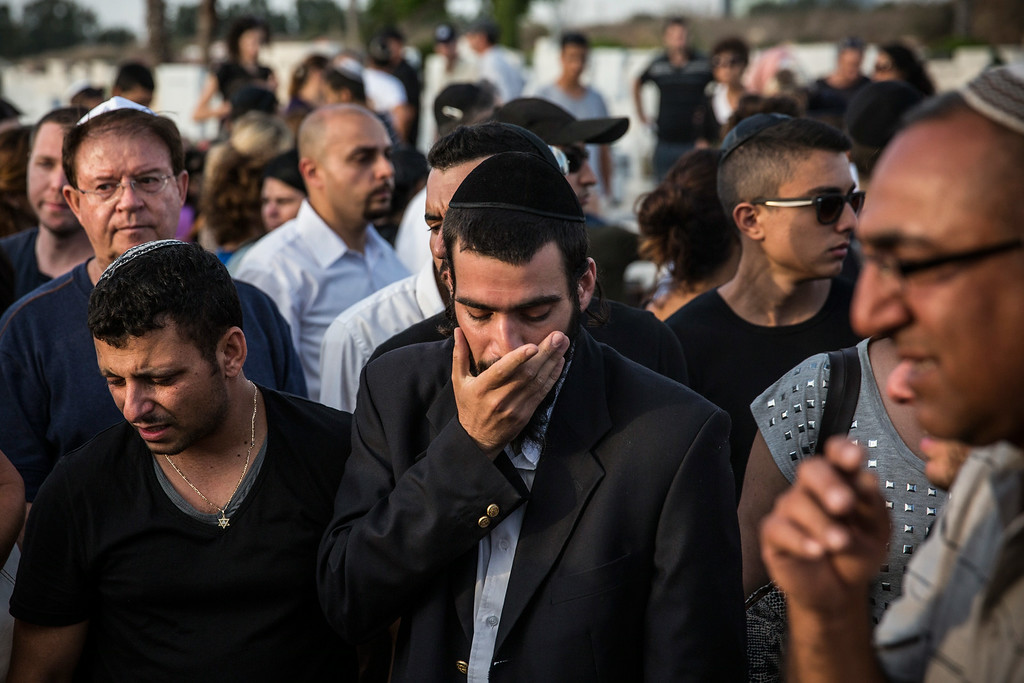 ". People mourn during the funeral of Dror Khenin at a cemetery on July 16, 2014 in Yahud Monoson, Israel. Yesterday Khenin was the first Israeli to be killed by a Hamas mortar as he offered food to Israeli soldiers working near the Erez border crossing between Israel and Gaza. As Operation ""Decisive Edge\"" enters its ninth day, over 200 Palestinians have been killed in Israeli missile strikes.  (Photo by Andrew Burton/Getty Images)"