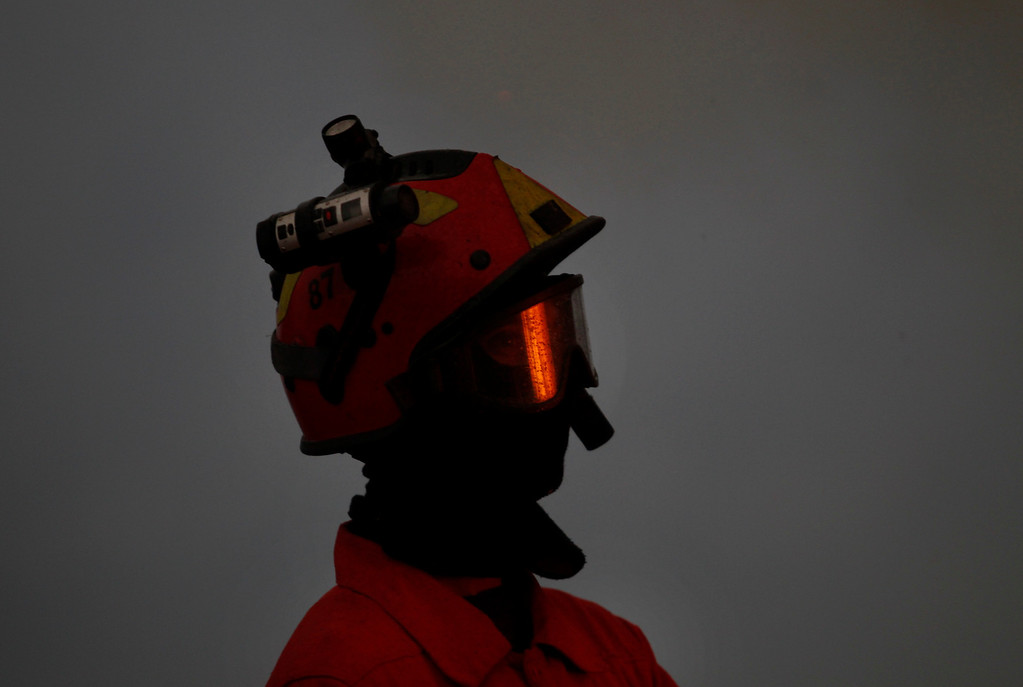 . A Portuguese firefighter surrounded by smoke works to extinguish a wildfire, reflected in goggles, near Caramulo, north Portugal, Thursday, Aug. 29, 2013. (AP Photo/Francisco Seco)