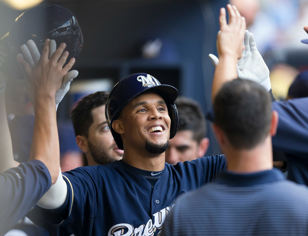 . Carlos Gomez of the Milwaukee Brewers is greeted by teammates in the dugout after hitting a two run home run off of Jhoulys Chacin of the Colorado Rockies during the first inning of a baseball game Saturday, June 28, 2014, in Milwaukee. (AP Photo/Tom Lynn)