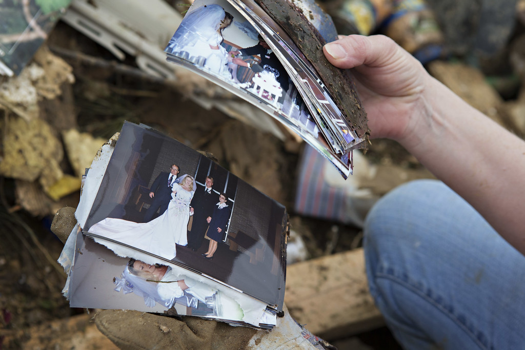 . Lisa Taney, a volunteer, goes through wedding photos found in the mud near a destroyed trailer after a strong tornado went through the area on April 27 for the second time in three years on April 28, 2014 in Vilonia, Arkansas. After deadly tornadoes ripped through the area and have left over a dozen dead, Mississippi, Arkansas, Texas, Louisiana, and Tennessee are all under watch as multiple storms over the next few days are expected.  (Photo by Wesley Hitt/Getty Images)