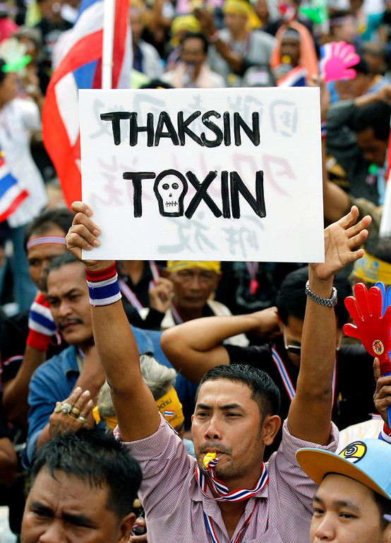 . Thai anti-government protester holds placard against former premier Thaksin Shinawatra during a rally occupying the Finance Ministry in Bangkok, Thailand, 26 November 2013.  EPA/RUNGROJ YONGRIT