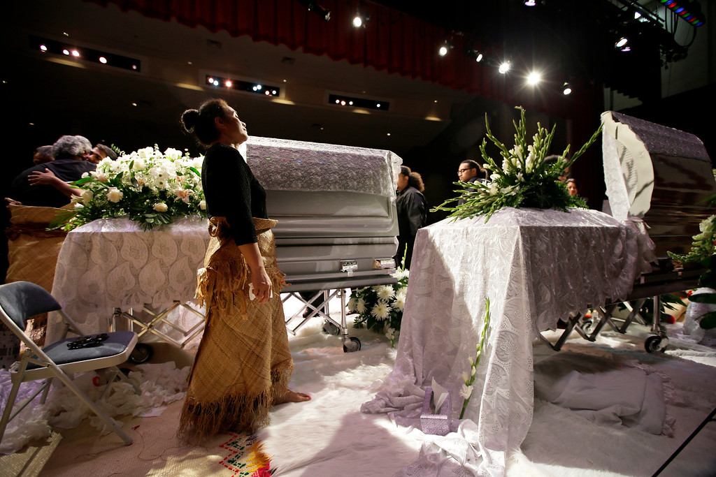 """. Hinemoa Garcia, front, stands by the caskets of her nephews Polo Manukainiu, right, a Texas A&M redshirt freshman, and Andrew \""""Lolo\"""" Uhatafe, left, during a memorial service at Trinity High School, Friday, Aug. 9, 2013, in Euless, Texas. More than 2,500 people showed up to mourn the two who were killed in a single car accident in New Mexico, on July 29. Also killed in the accident was 18-year-old Utah recruit Gaius \""""Keio\"""" Vaenuku. (AP Photo/Tony Gutierrez)"""