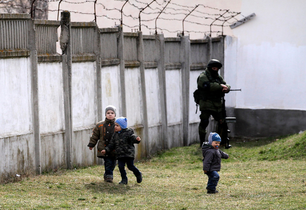 . A Russian soldier watches children as he and comrades block the Ukraine\'s infantry base in Perevalne, Ukraine, Tuesday, March 4, 2014. Russian President Vladimir Putin said Moscow reserves the right to use all means to protect Russians in Ukraine as U.S. Secretary of State John Kerry was on his way to Kiev. Tensions remained high in the strategic Ukrainian peninsula of Crimea with troops loyal to Moscow firing warning shots to ward off protesting Ukrainian soldiers. (AP Photo/Darko Vojinovic)