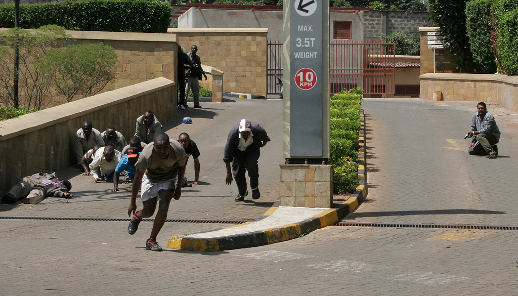 . A body, left, lies outside the Westgate Mall, an upscale shopping mall  in Nairobi, Kenya Saturday Sept. 21 2013, where shooting erupted when armed men attempted to rob a shop, according to police. Witnesses say a half dozen grenades also went off along with volleys of  gunfire in and around the mall.  (AP Photo/Sayyid Azim)