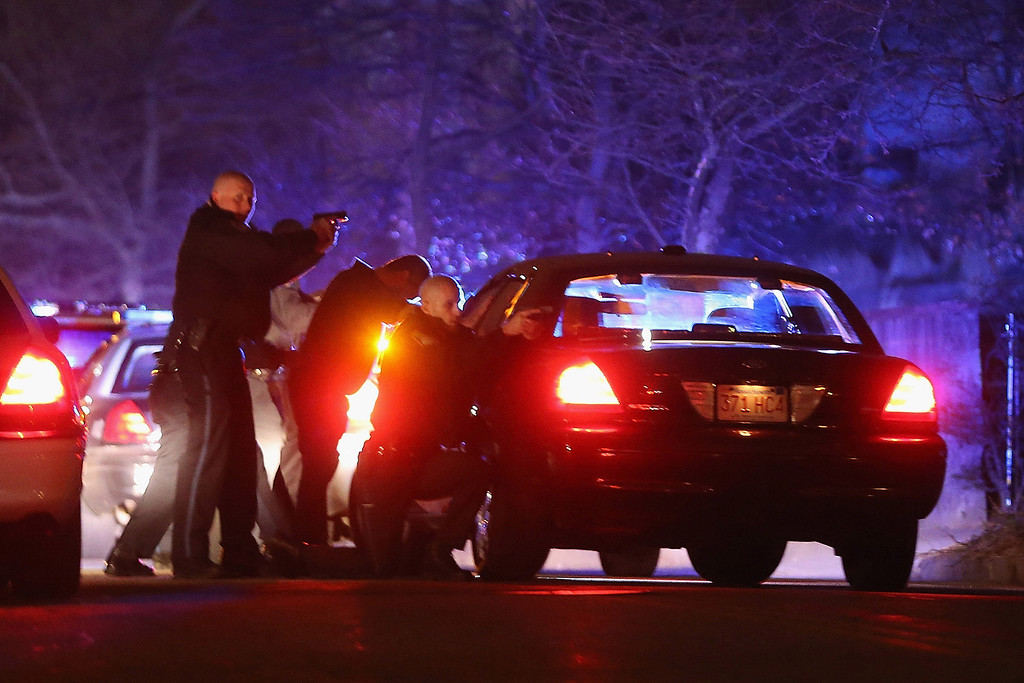 . WATERTOWN, MA - APRIL 19:  Police with guns drawn search for a suspect on April 19, 2013 in Watertown, Massachusetts.  Earlier, a Massachusetts Institute of Technology campus police officer was shot and killed late Thursday night at the school\'s campus in Cambridge. A short time later, police reported exchanging gunfire with alleged carjackers in Watertown, a city near Cambridge. It\'s not clear whether the shootings are related or whether either are related to the Boston Marathon bombing.  (Photo by Mario Tama/Getty Images)