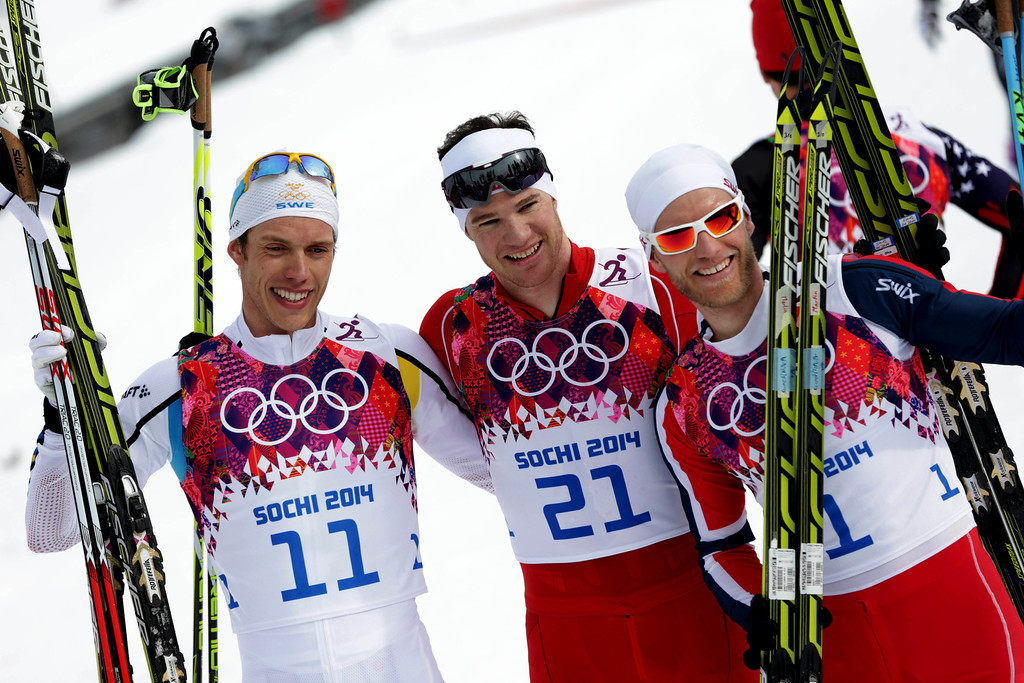 . Switzerland\'s Dario Cologna, center, winner of the men\'s cross-country 30k skiathlon, celebrates with silver medalist Sweden\'s Marcus Hellner, left, and bronze medalist Norway\'s Martin Johnsrud Sundby, at the 2014 Winter Olympics, Sunday, Feb. 9, 2014, in Krasnaya Polyana, Russia. (AP Photo/Matthias Schrader)