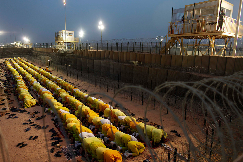 . Detainees pray at a U.S. military detention facility Camp Bucca, Iraq, Monday, March 16, 2009. The United States aimed to shut down its largest detention center, Camp Bucca, by 2010. More than 9,600 detainees who were captured as national security threats were being held there; at its peak, the prison located 340 miles southeast of Baghdad held 26,000 detainees. (AP Photo/Dusan Vranic)