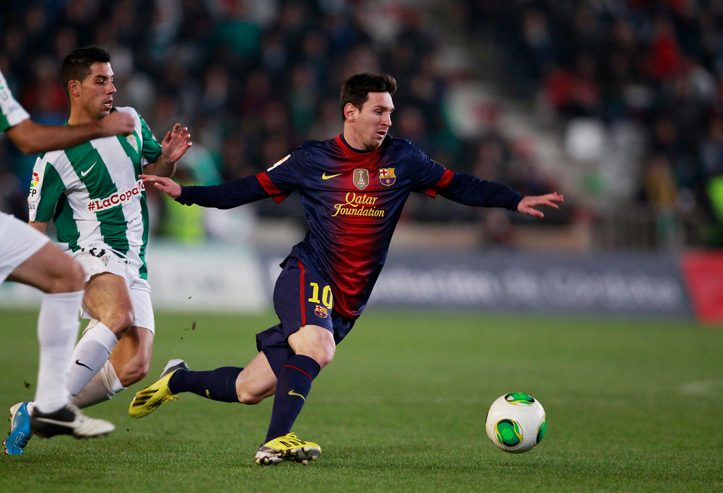 . Barcelona\'s Lionel Messi is challenged by Cordoba\'s Carlos Caballero (L) during their Spanish King\'s Cup soccer match at Nuevo Arcangel stadium in Cordoba December 12, 2012. REUTERS/Marcelo del Pozo