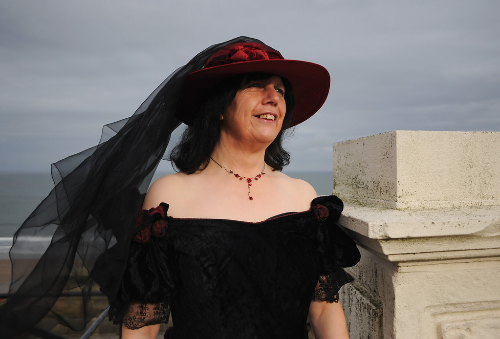 . WHITBY, ENGLAND - NOVEMBER 02: Catheryn Messenger from Scarborough works for the charity Age UK. She visits the Goth weekend dressed in Victorian style on November 2, 2013 in Whitby, England. The Whitby Gothic Weekend that takes place in the Yorkshire seaside town twice yearly in Spring and Autumn started in 1994 and sees thousands of extravagantly dressed followers of Victoriana, Steampunk, Cybergoth and Romanticism visit to take part in celebrating Gothic culture.  (Photo by Ian Forsyth/Getty Images)