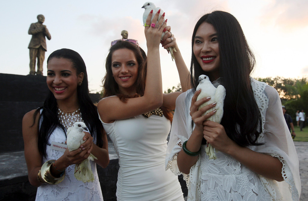 . Miss World 2012 Yu Wenxia  of China, right, Miss Macedonia Fyro Kristina Spasenoska, center, and Miss Trinidad and Tobago Sherrece Villafana, left, hold doves during the International World Peace Day celebrations at a park in Denpasar, Bali, Indonesia on Saturday, Sept. 21, 2013. The Miss World pageant final will be held in Bali on Sept. 28. (AP Photo/Firdia Lisnawati)