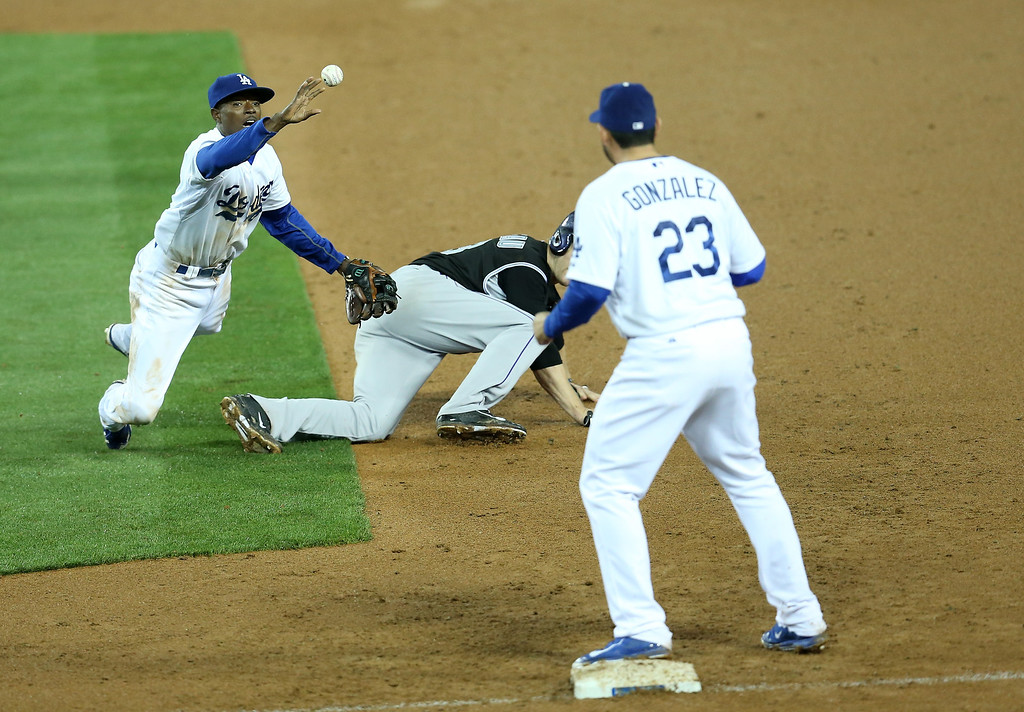 . LOS ANGELES, CA - APRIL 25: Second baseman Dee Gordon #9 of the Los Angeles Dodgers flips the ball to first baseman Adrian Gonzalez #23 to complete a double play after tagging out Justin Morneau #33 of the Colorado Rockies to end the top of the 11th inning at Dodger Stadium on April 25, 2014 in Los Angeles, California. The Rockies won 5-4 in 11 innings.  (Photo by Stephen Dunn/Getty Images)