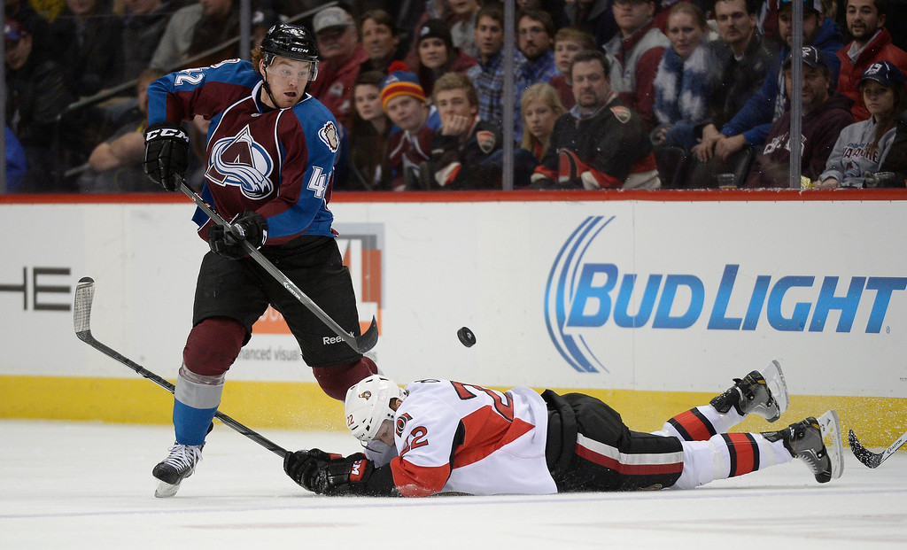 . Colorado Avalanche center Brad Malone (42) watches as the puck sails over a fallen Ottawa Senators right wing Erik Condra (22) during the first period January 8, 2014 at Pepsi Center. (Photo by John Leyba/The Denver Post)