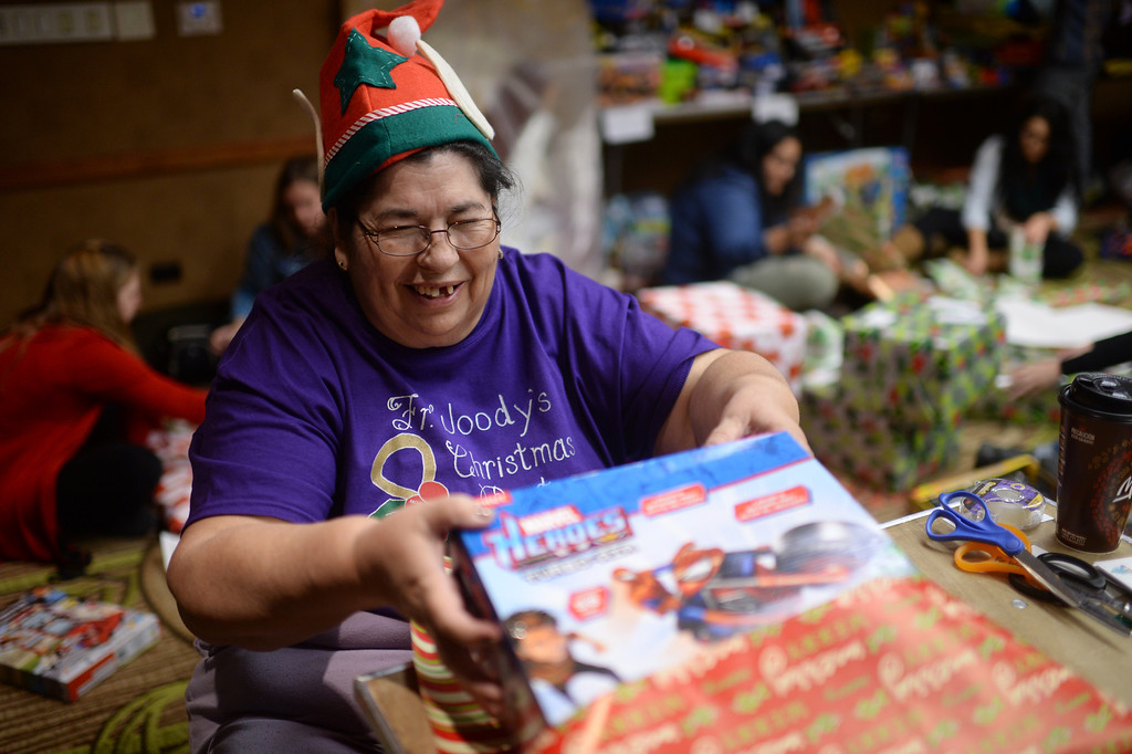 """. DENVER, CO. DECEMBER 21: Barbara Tolmich of Denver is wrapping Christmas gift during the annual Father Woody Christmas Party in Denver, Colorado December 21, 2013. In advance of handing out 5,000 gifts, volunteers are doing a \""""wrapping party\"""" at the Sheraton Denver Downtown Hotel. (Photo by Hyoung Chang/The Denver Post)"""