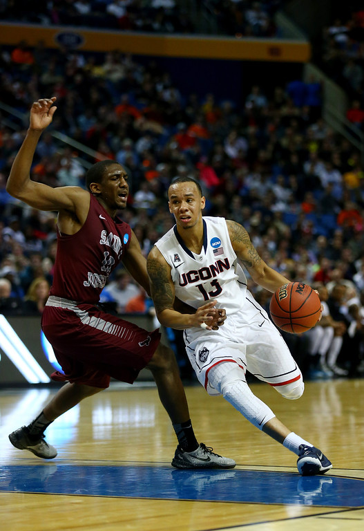 . BUFFALO, NY - MARCH 20: Shabazz Napier #13 of the Connecticut Huskies drives to the basket as Langston Galloway #10 of the Saint Joseph\'s Hawks defends during the second round of the 2014 NCAA Men\'s Basketball Tournament at the First Niagara Center on March 20, 2014 in Buffalo, New York.  (Photo by Elsa/Getty Images)