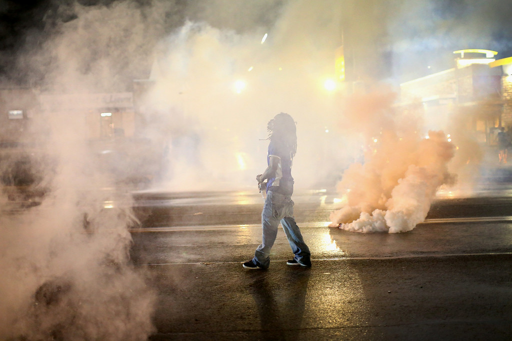 . FERGUSON, MO - AUGUST 15:  A demonstrator walks through smoke launched by police after a skirmish on August 15, 2014 in Ferguson, Missouri. Police sprayed pepper spray, shot smoke, gas and flash grenades at protestors before retreating. Several businesses were looted following the skirmish as police held their position nearby. Violent outbreaks have taken place in Ferguson since the shooting death of Michael Brown by a Ferguson police officer on August 9.  (Photo by Scott Olson/Getty Images)