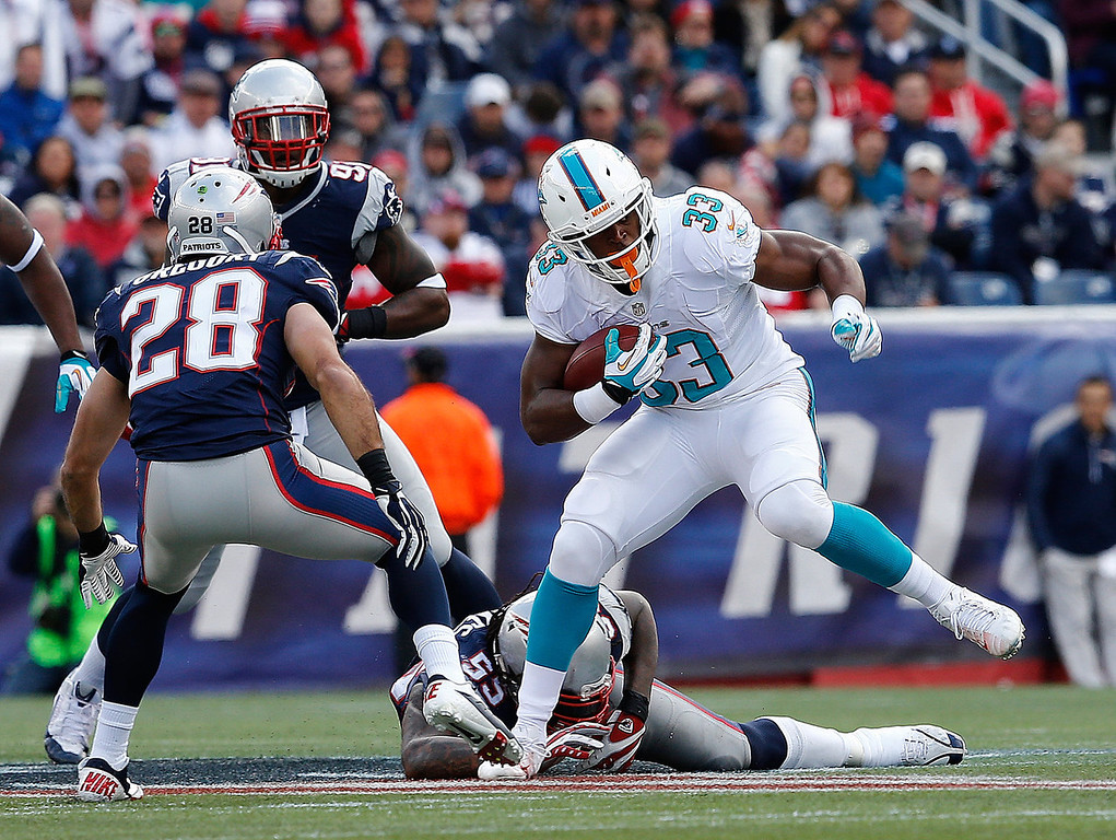 . Daniel Thomas #33 of the Miami Dolphins yards the ball against the New England Patriots in the first half at Gillette Stadium on October 27, 2013 in Foxboro, Massachusetts. (Photo by Jim Rogash/Getty Images)