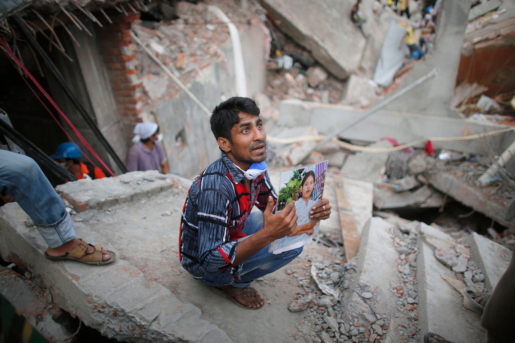 . A relative holds up a picture of a garment worker in front of the rubble of the collapsed Rana Plaza building, in Savar, 30 km (19 miles) outside Dhaka April 27, 2013. Two factory bosses and two engineers were arrested in Bangladesh on Saturday, 72 hours after the collapse of a building where low-cost garments were made for Western brands, as the death toll rose to 340 but many were still being found alive. REUTERS/Andrew Biraj
